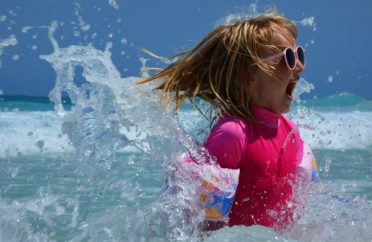 Child splashing in the sea on holiday