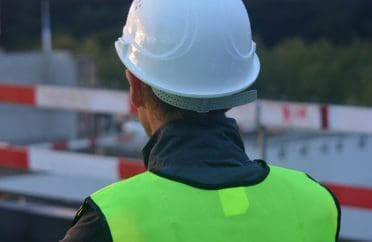 Construction worker looking away at site, wearing safety helmet and high visibility jacket