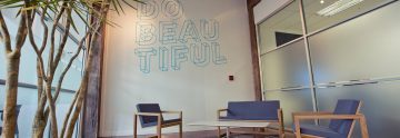 Photo of trendy office, with 'Do Beautiful' message on wall'