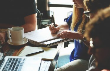 Close-up photo of office meeting showing notepads and coffee cups