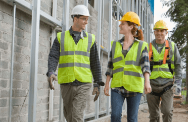 Photo of three people walking through building site wearing high viz and safety hats / boots