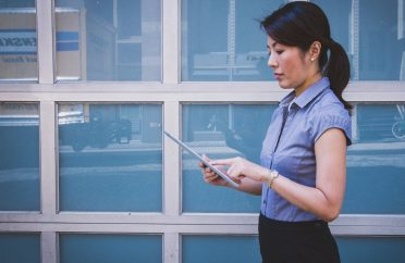 Photo of woman in business attire with ipad considering her directors remuneration package