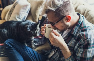 Photo of man in his comfort zone - drinking coffee on the sofa with his cat
